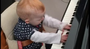 Cute one year old child plays a piano concert