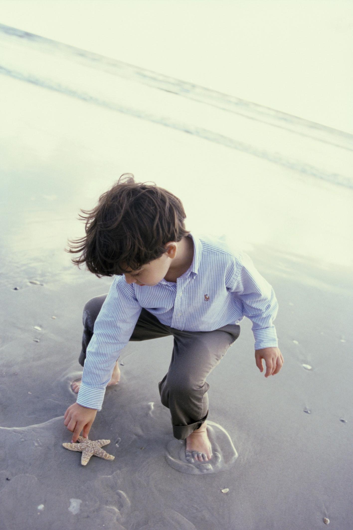 boy picking up starfish