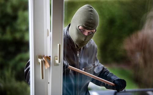 A thief breaking in the door.