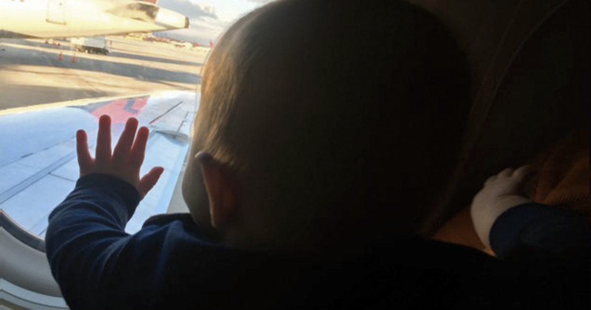 Stranger Held An Exhausted Dad's Son On A Plane So He Could Rest